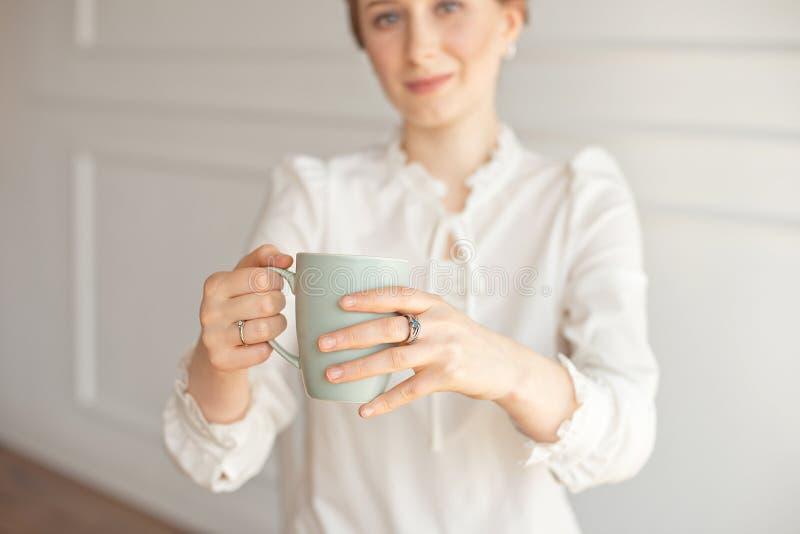 Menina na camisa clássica branca do negócio do estilo que guarda um copo do café ou do chá quente em suas mãos fotos de stock royalty free