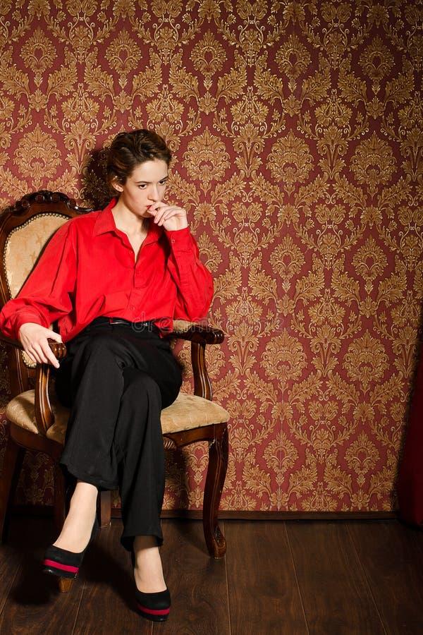 Menina na camisa masculina vermelha. No interior retro fotografia de stock