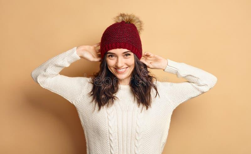 Menina na camiseta e em Beanie Hat feitos malha sobre o fundo bege fotos de stock