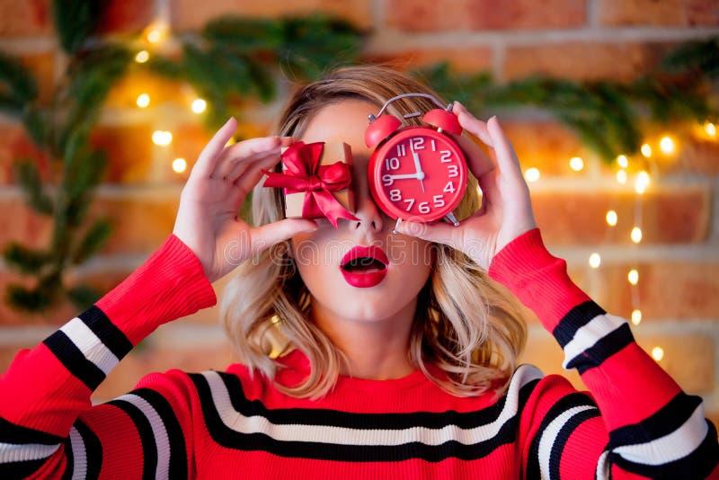 Menina na camiseta listrada vermelha com caixa de presente e despertador fotos de stock