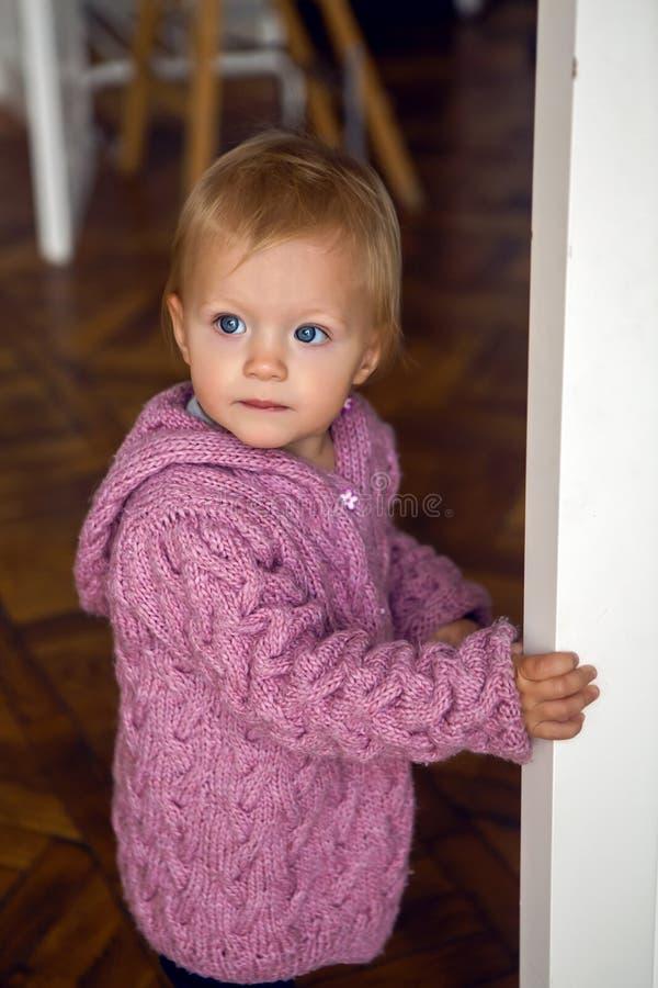 A menina na camiseta roxa com a capa está em casa na entrada foto de stock