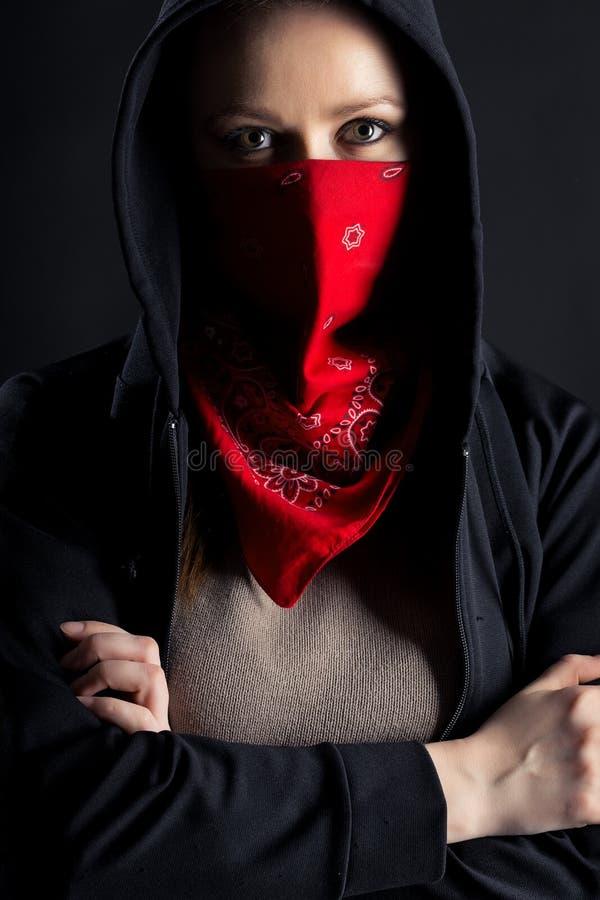 Menina na capa preta com um xaile vermelho em sua cara imagem de stock royalty free