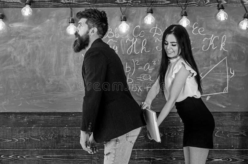 Menina na cara de sorriso que tem o divertimento quando punir o professor Senhora do estudante que golpeia nas nádegas dos profes imagem de stock