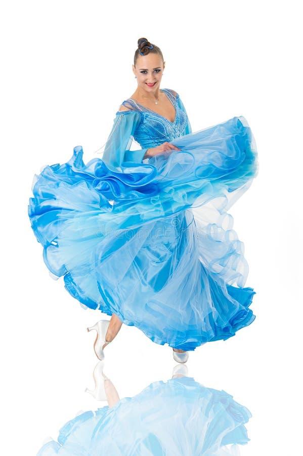 Menina na cara de sorriso vestida no vestido azul luxuoso que levanta com postura O dançarino da dança de salão de baile olha lin fotografia de stock