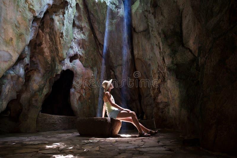 Menina na caverna sob raios do sol imagem de stock