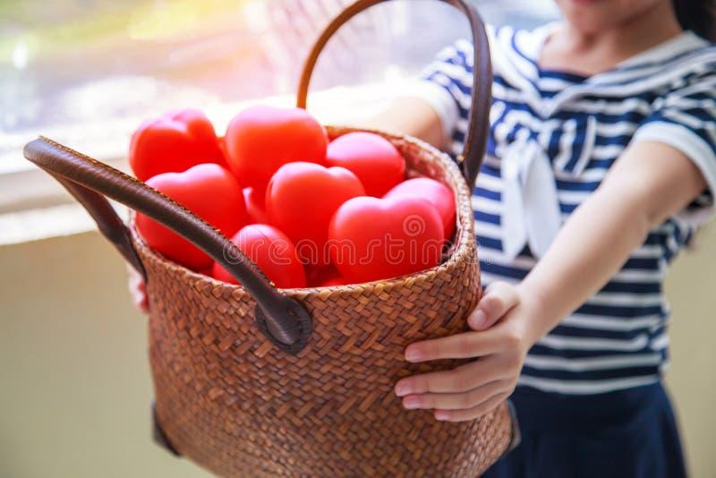 A menina na cesta entregando do vestido listrado dos azuis marinhos de corações vermelhos representa as mãos amiga, apoio da famí foto de stock royalty free