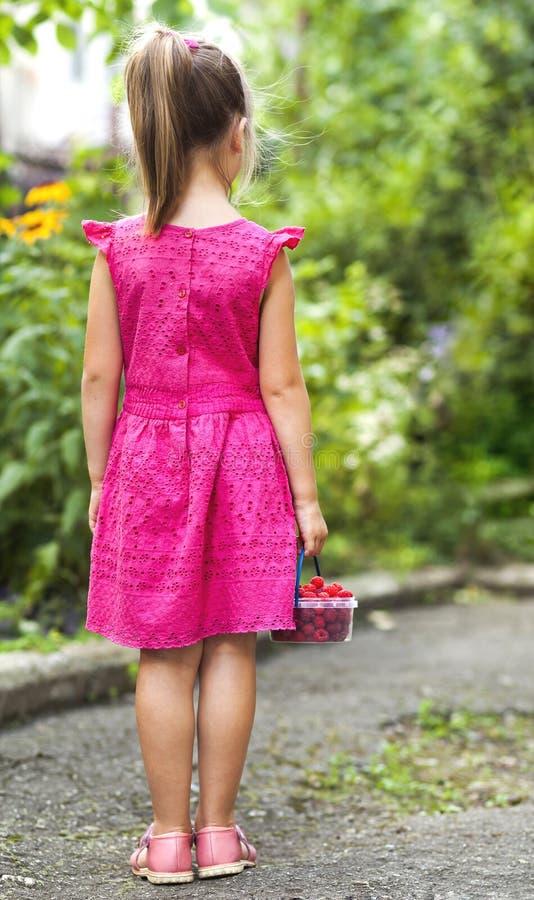 Menina na cesta pequena do holdind da mão da criança do vestido de ras maduros foto de stock