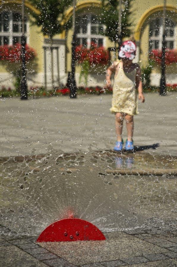 Menina na cidade quente do verão com sistema de extinção de incêndios da água foto de stock royalty free