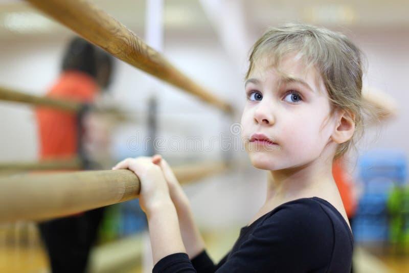 Menina na classe do bailado perto do frame e do grande espelho fotografia de stock