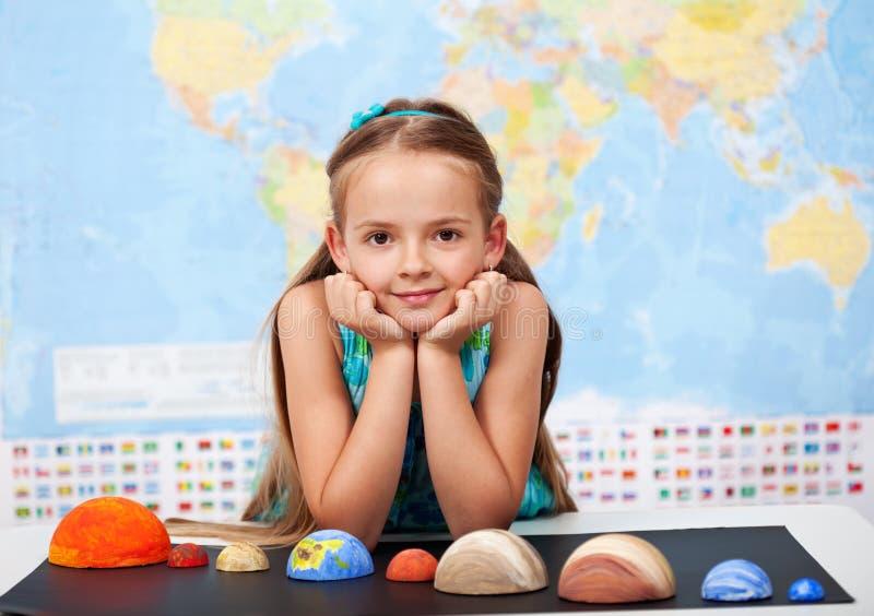 Menina na classe elementar da ciência com seu projeto home fotografia de stock