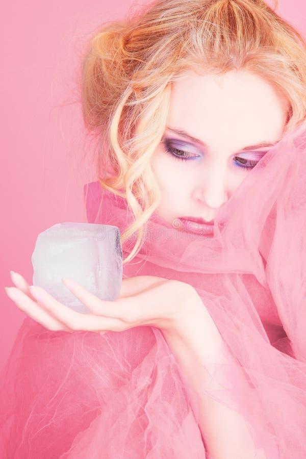 Menina na cor-de-rosa com cubo de gelo imagem de stock