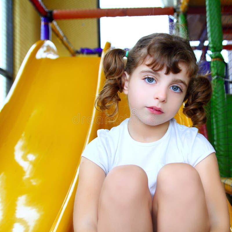 Menina na corrediça colorida do amarelo do campo de jogos imagens de stock royalty free