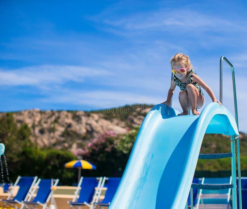 Menina na corrediça de água no aquapark no verão fotografia de stock