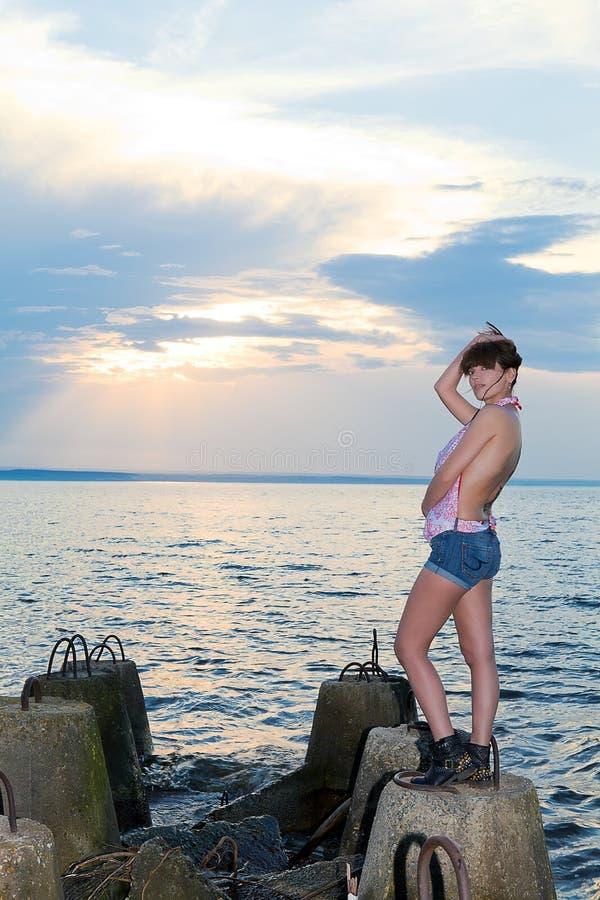 Menina na costa do golfo com estruturas concretas imagens de stock royalty free