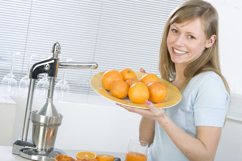 Menina na cozinha com laranja suculenta fotos de stock royalty free