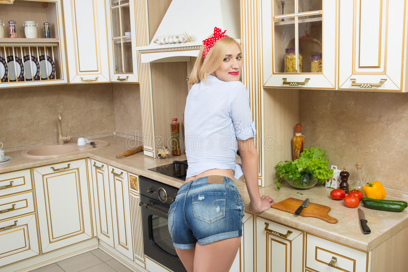 Menina na cozinha no short curto fotos de stock royalty free