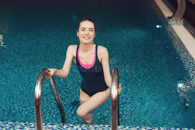 Menina na escada da associação no gym Olha feliz, elegante e apta em uma parte foto de stock