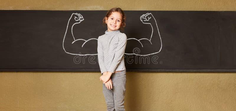 Menina na escola primária com os músculos no quadro-negro imagens de stock royalty free