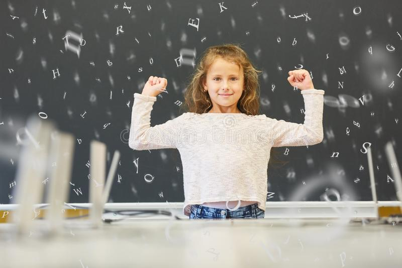 Menina na escola primária na frente do quadro-negro com letras imagens de stock royalty free