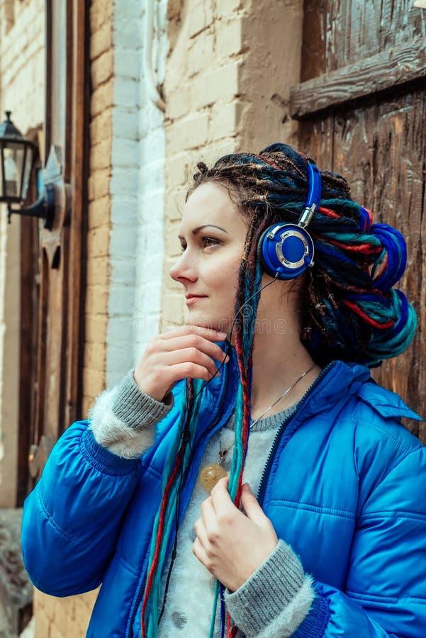 Menina na escuta azul a música em fones de ouvido foto de stock royalty free