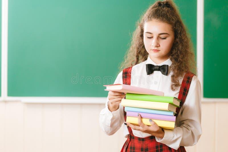 Menina na farda da escola que está perto do quadro-negro com livros Estudante na classe na escola fotos de stock royalty free