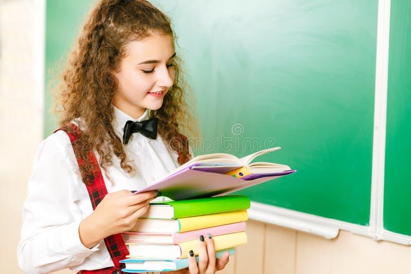 Menina na farda da escola que está perto do quadro-negro com livros Estudante na classe na escola fotos de stock