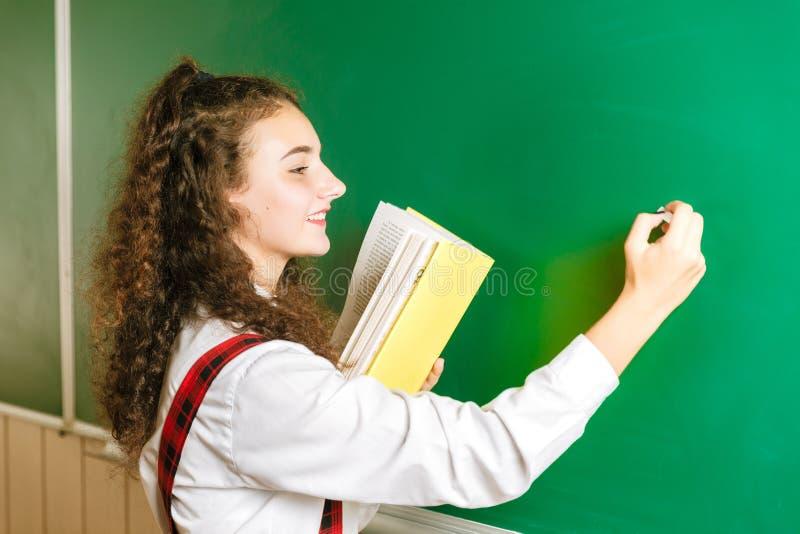 Menina na farda da escola que está perto do quadro-negro com livros Estudante na classe na escola imagem de stock royalty free