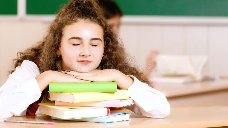 Menina na farda da escola que senta-se em sua mesa na sala de aula com livros Estudante na classe na escola fotos de stock