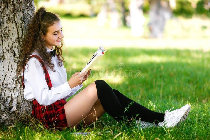 A menina na farda da escola que senta-se perto de uma árvore no parque e aprende lições Menina que lê um livro ao ar livre fotos de stock royalty free