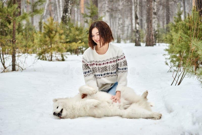 Menina na floresta do inverno que anda com um cão A neve está caindo fotos de stock royalty free