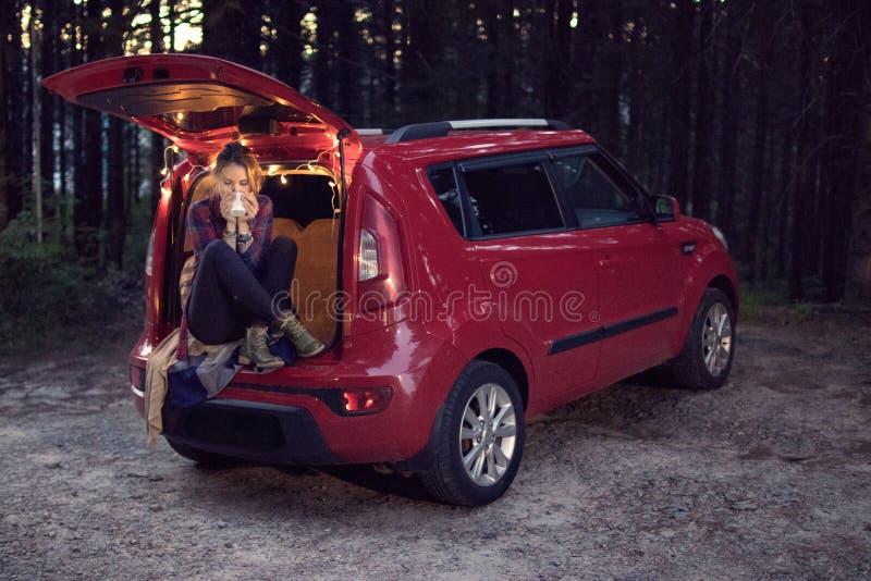 Menina na floresta na noite que senta-se no tronco de um carro vermelho w foto de stock royalty free