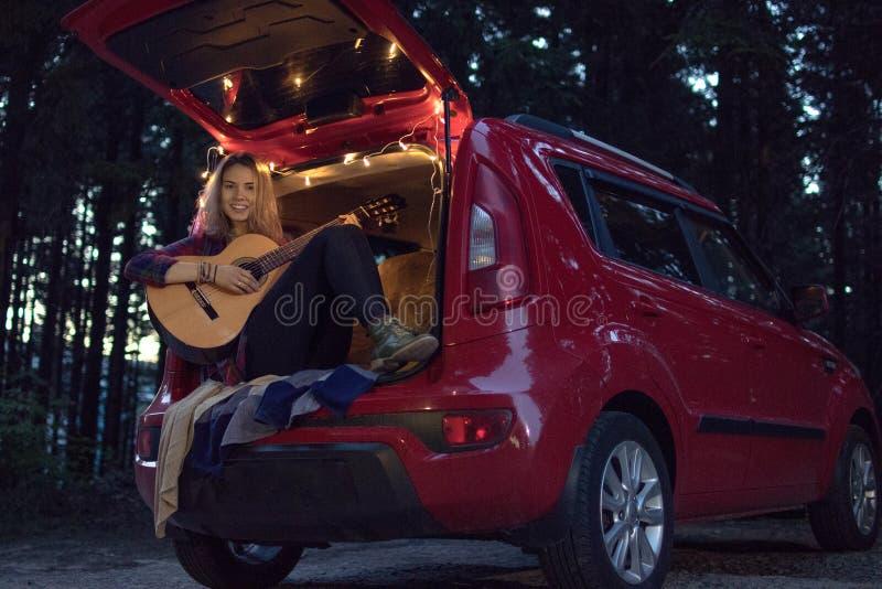 Menina na floresta na noite que senta-se no tronco de um carro vermelho w imagens de stock