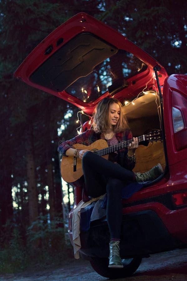 Menina na floresta na noite que senta-se no tronco de um carro vermelho w fotografia de stock royalty free