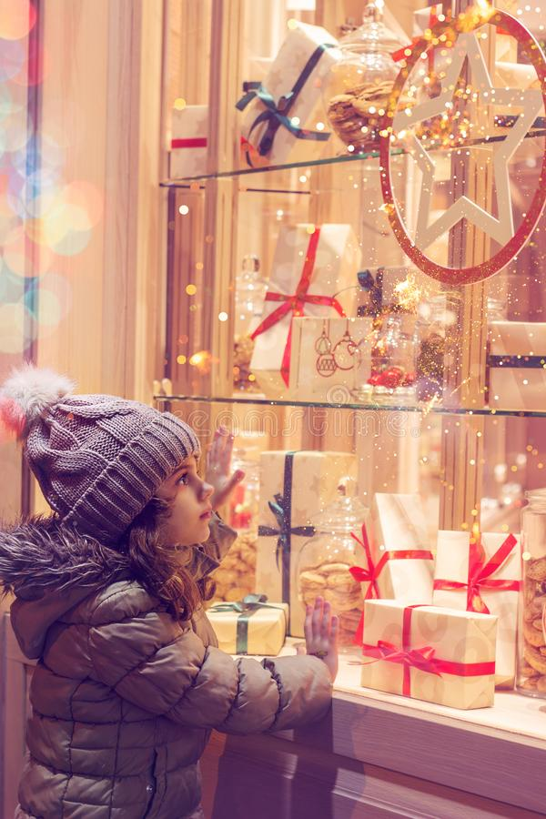 Menina na frente da janela de uma loja, completa de presentes envolvidos fotografia de stock