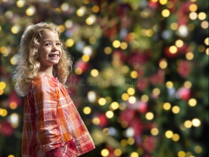 Menina na frente de uma árvore dos chrismas foto de stock royalty free