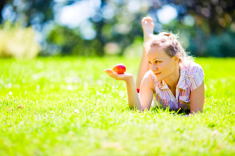 Menina na grama verde que olha na maçã vermelha foto de stock
