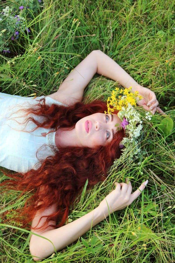 A menina na grinalda encontra-se na grama e olha-se acima no prado na soma imagem de stock royalty free