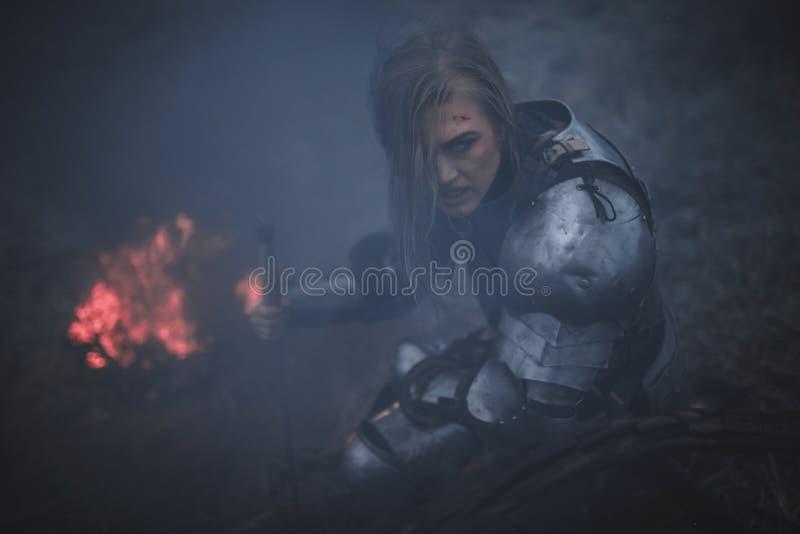 A menina na imagem do arco do ` de Jeanne d na armadura e com a espada em suas mãos ajoelha-se contra o fundo do fogo e do fumo fotos de stock