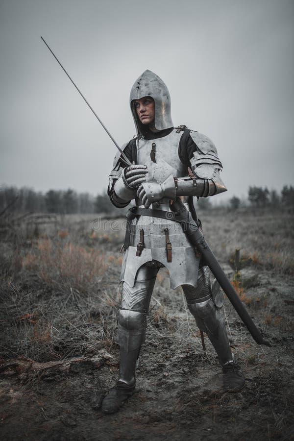 A menina na imagem do arco do ` de Jeanne d vai no prado na armadura e no capacete com a espada em suas mãos fotos de stock royalty free