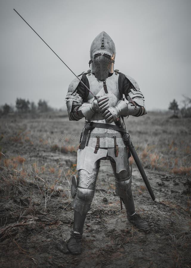 A menina na imagem do arco do ` de Jeanne d vai no prado na armadura e no capacete com viseira fechado e espada em suas mãos imagens de stock