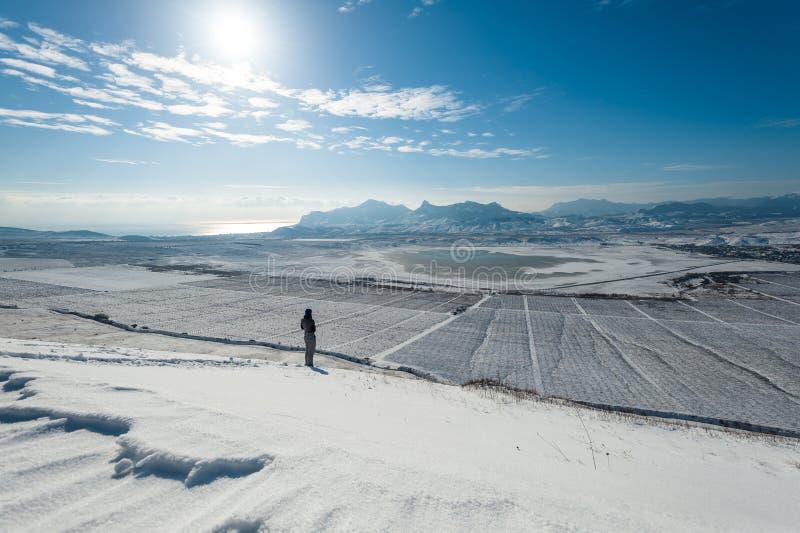 Menina na inclinação nevado com montanhas e o mar no fundo foto de stock royalty free
