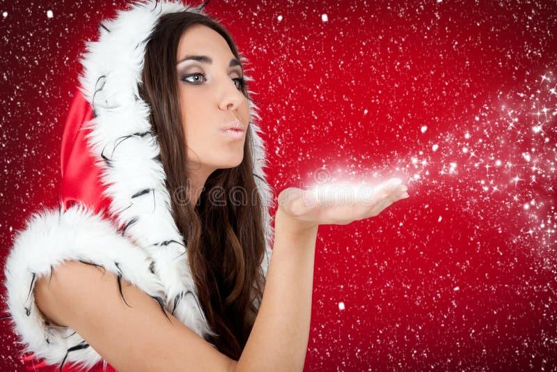 Menina na mão de sopro do formulário da neve do traje do Natal foto de stock