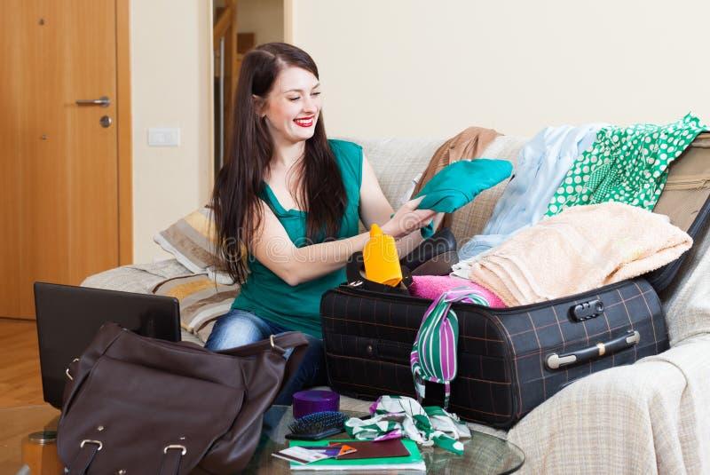 Menina na mala de viagem da embalagem do sofá para o feriado foto de stock