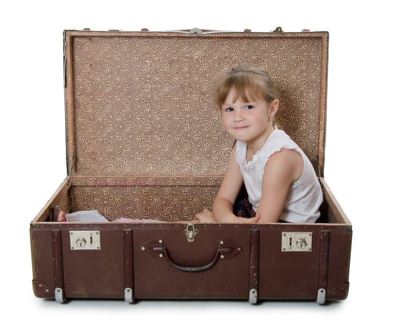 A menina na mala de viagem velha fotos de stock royalty free