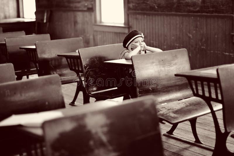 Menina na mesa antiga da escola fotografia de stock