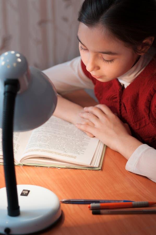 Menina na mesa que lê um livro pela luz da lâmpada fotografia de stock royalty free