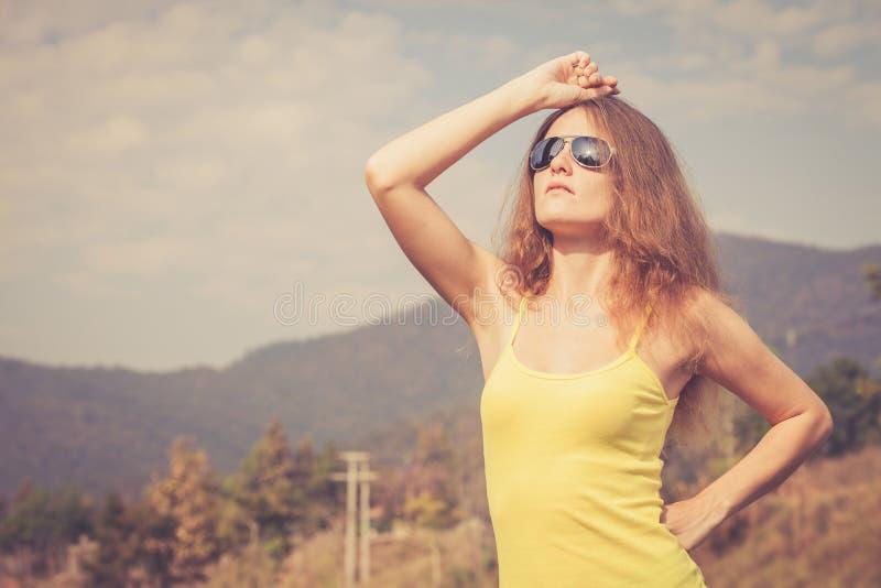 Menina na moda do moderno nos óculos de sol que relaxam na estrada no th foto de stock royalty free