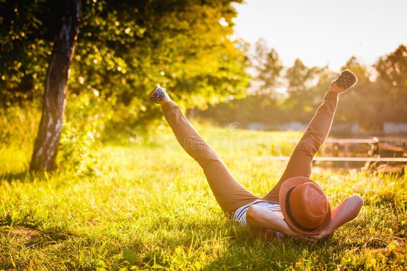 Menina na moda do moderno que relaxa na grama imagem de stock