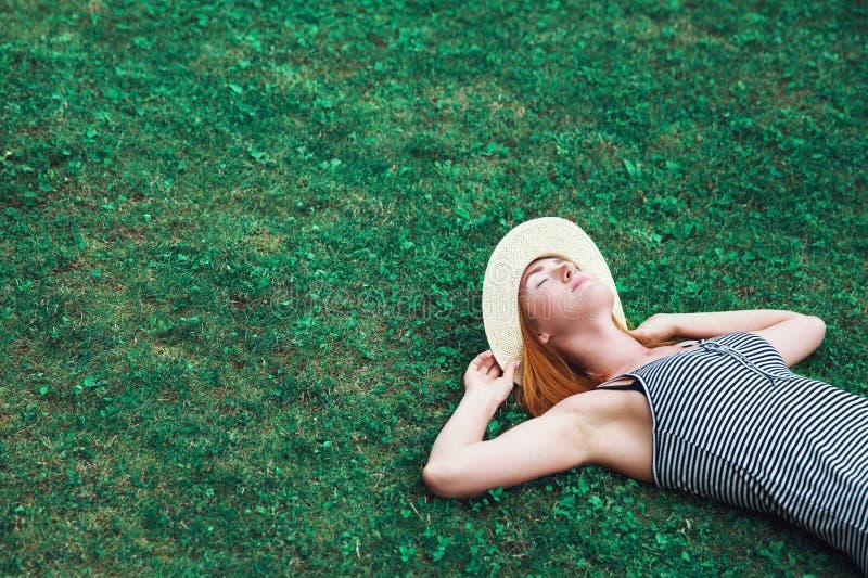 Menina na moda do moderno que relaxa na grama imagem de stock royalty free