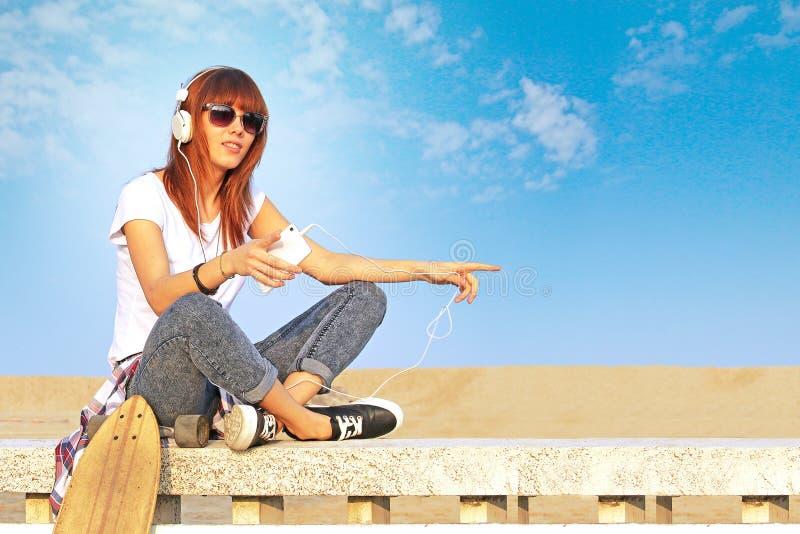 A menina na moda escuta a música com smartphone fotos de stock royalty free